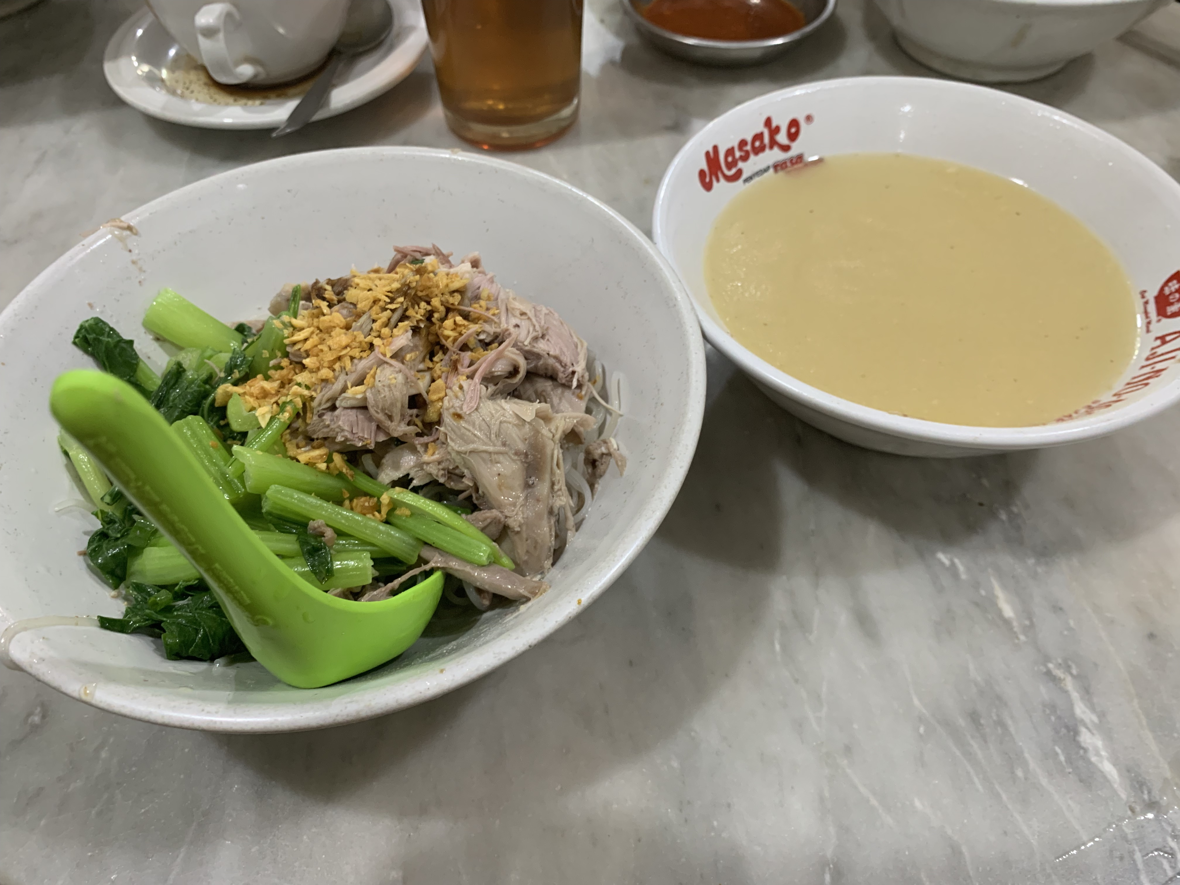 Image shows a bowl of Indonesian duck noodles and a bowl of homemade soup