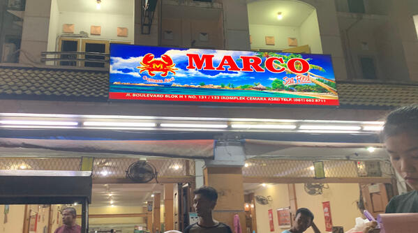 """Image shows a restaurant shopfront featuring a """"Marco"""" signboard"""