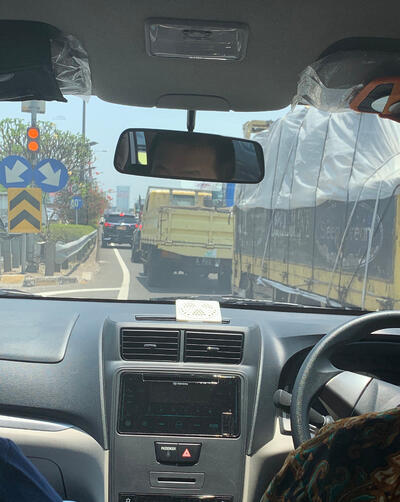 Image shows the sight of traffic congestion from a back passenger point of view