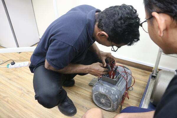 an image showing a technician getting hands-on with electric motor testing