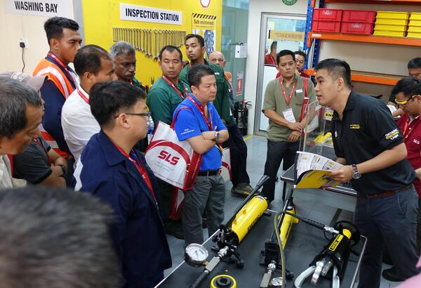 Image shows an Enerpac engineer conducting a live demo of hydraulic tools to a group of customers