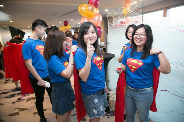 Image shows a group of people dressed in a Superman tee and cape
