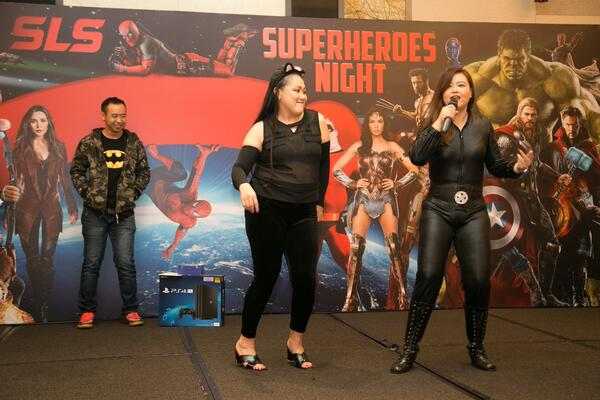 Image shows two women dressed in black on stage