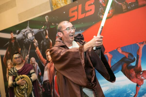Image shows a man with a lightsaber dressed as a Jedi