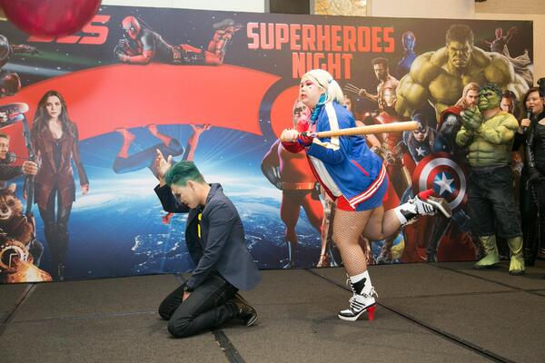 Image shows a man and a woman dressed as Joker and Harley Quinn on stage