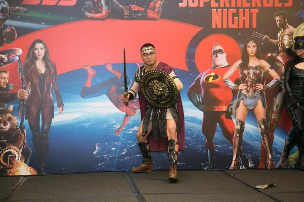 Image shows a man dressed as a Trojan warrior on stage