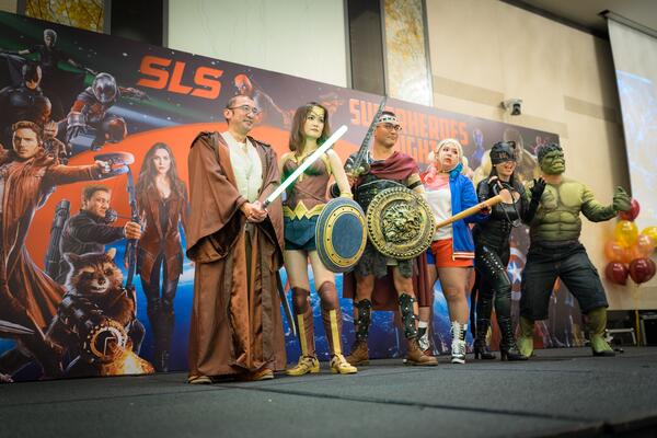 Image shows a group of people on stage dressed as superheros