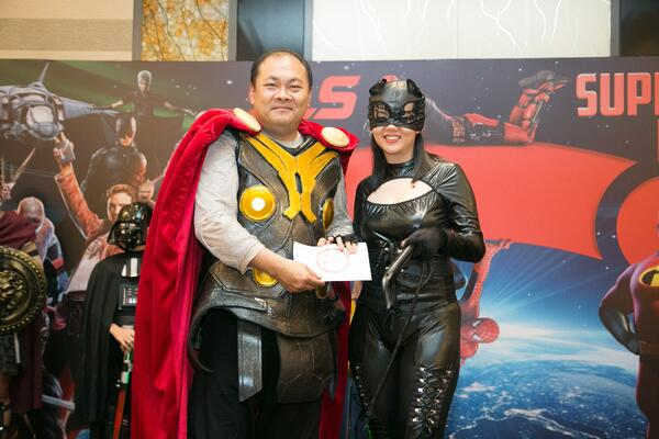 Image shows Group CEO Mr. Roy Tan presenting an award to a woman dressed as Cat Woman