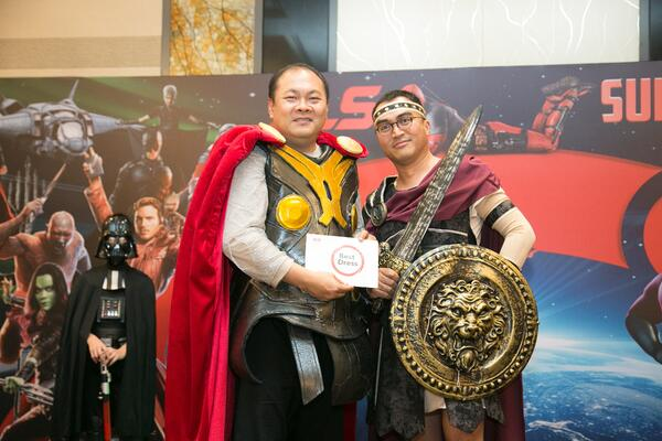 Image shows SLS Group CEO presenting a Best Dressed award to a man dressed as a Trojan warrior