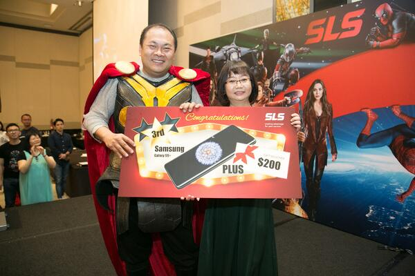 Image shows SLS Group CEO Mr. Roy Tan presenting a prize to a woman