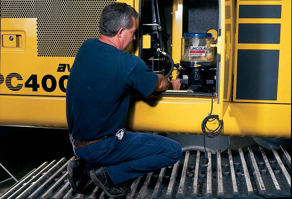 Image shows a man crouching in front of a lubrication system